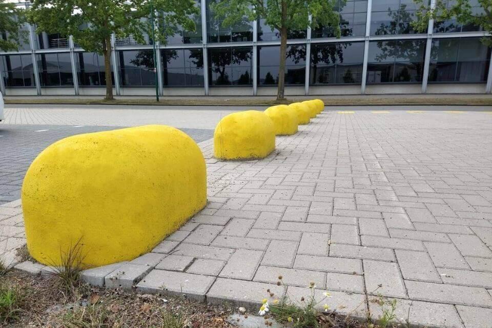 Gele jumboblokken beton als wegafscheiding
